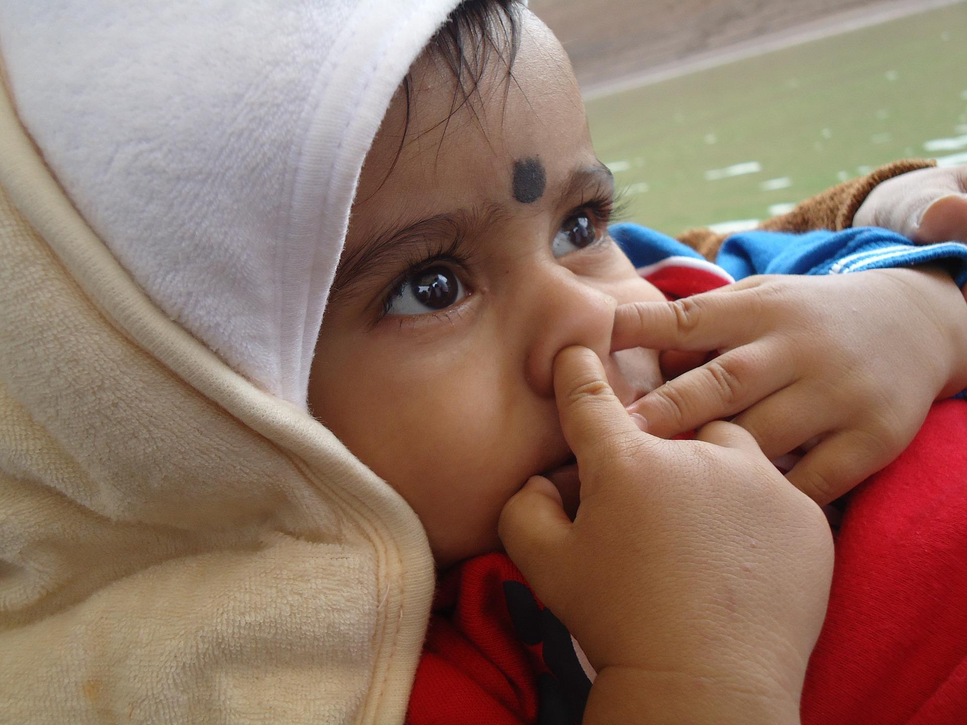 Kleinkind steckt sich Finger in die Nase